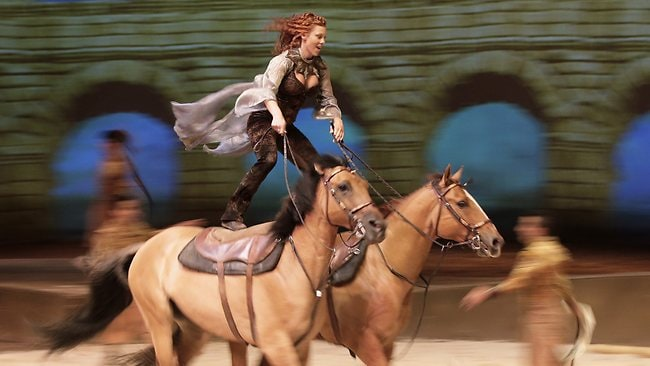 "Fairland Ferguson rides while standing on the backs of a pair of horses during a dress rehearsal for the show ""Cavalia"" in Sydney. Picture: AP"
