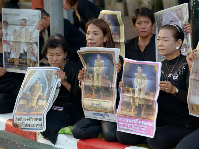 Women hold images of Thai Crown Prince Maha Vajiralongkorn outside the Grand Palace in Bangkok. Picture: AFP.