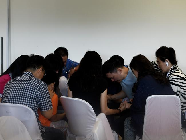 Family members of passengers pray together while waiting for a briefing inside the crisis-centre set up at Juanda International Airport in Surabaya. Picture: Manan Vatsyayana