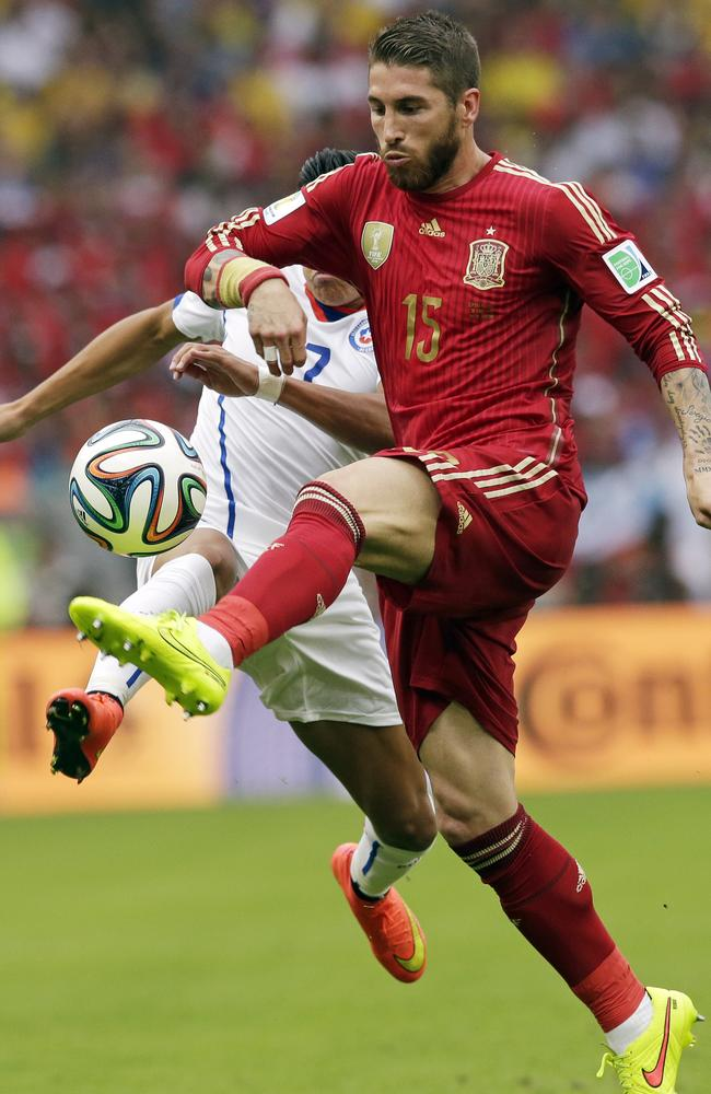 Spain's Sergio Ramos is challenged by Chile's Alexis Sanchez.