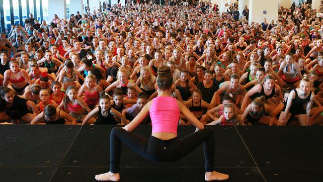 Star of the US show Dance Moms Abby Lee Miller and Maddie Ziegler pictured at Randwick Racecourse where they held a dance master class for thousands of screaming tween fans. Maddie leads the master class in some stretches. Picture: Toby Zerna