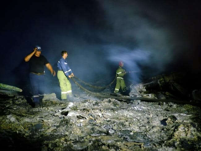 No sign of life ... firefighters spray water to extinguish a fire among the plane's wreckage.
