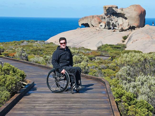 Scott Crowley in a wheelchair on a beach boardwalk, with vegetation around the outside of the walk and the rocks and sea behind him