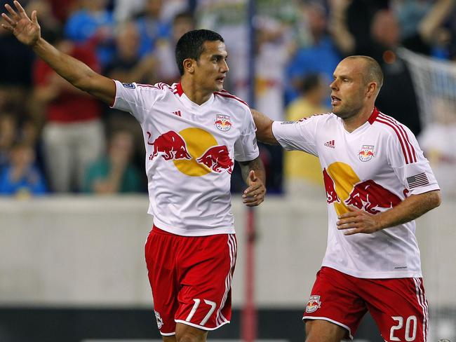 Tim Cahill is congratulated by teammate Joel Lindpere after scoring.