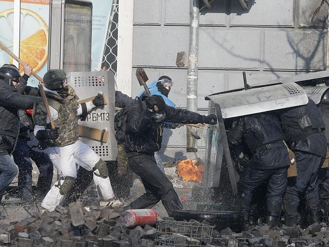Attacking with batons and shovels ... Anti-government protesters clash with riot police. Picture: AP Photo/Efrem Lukatsky