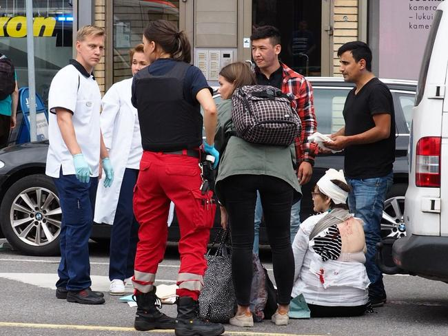 People and rescuers stand next to two persons sitting in a street in the Finnish city of Turku where several people were stabbed. Picture: AFP