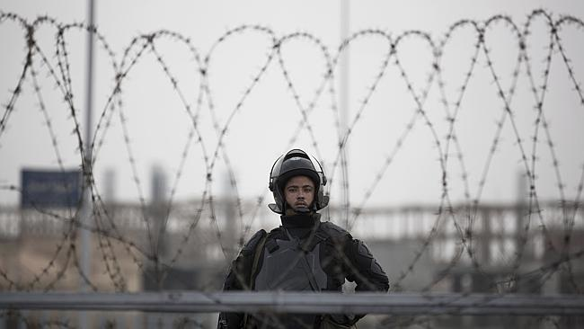 A riot policeman stands guard behind barbed wire outside the police academy compound where the trial of Mohammed Morsi is taking place.