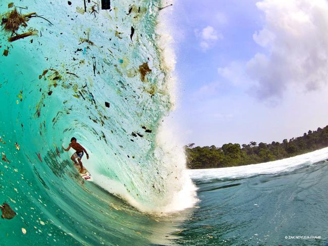 Trash surfer: Local surf champion Dede Suryana takes on the challenge of surfing through trash. Picture: Zak Noyle/zaknoyle.com