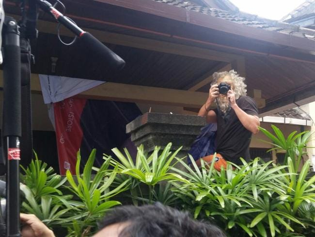 Michael Corby wearing a mask photographs media just before Schapelle Corby leaves her home in Kuta. Picture Supplied