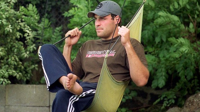 10/12/2002. Richmond star Brad Ottens sits in the hammock chair that caused him so much pain. While trying to hang the chair that he fell from the tree behind him and fell on a stake which got impaled on his leg.