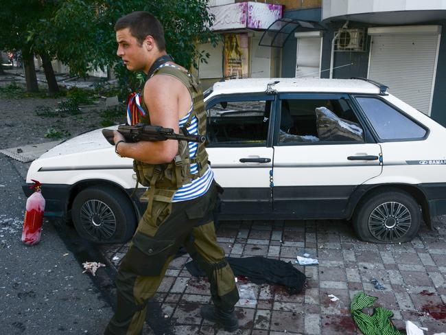 Ground force ... A Pro-Russian rebel passes by a car which was hit by shrapnel from a shell after shelling in the town of Donetsk, eastern Ukraine, yesterday. Source: AP