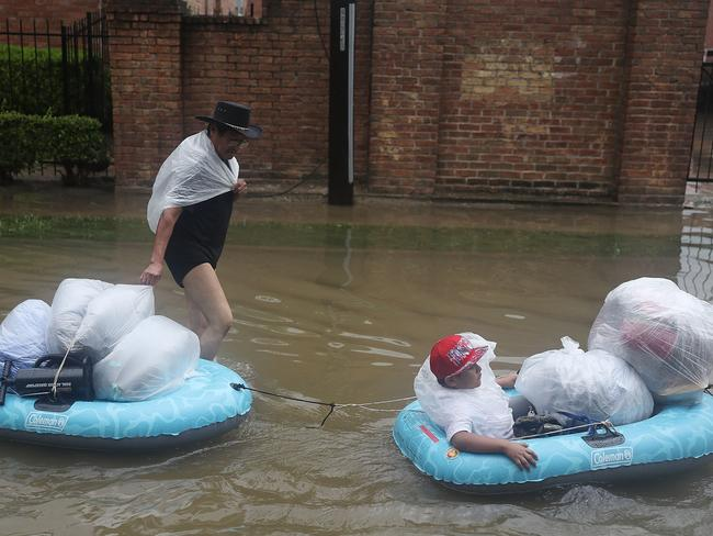 People walk down a flooded street as they evacuate their homes. Picture: Joe Raedle/Getty Images/AFP
