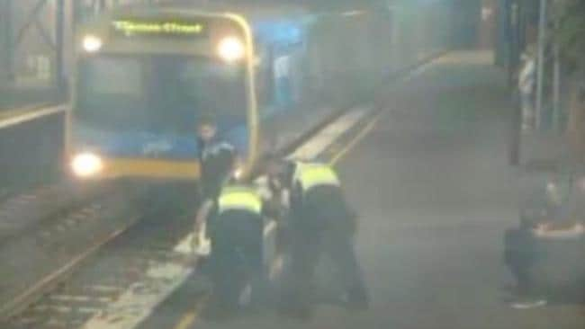 PSOs pull a woman up from the tracks. Picture: Victoria Police