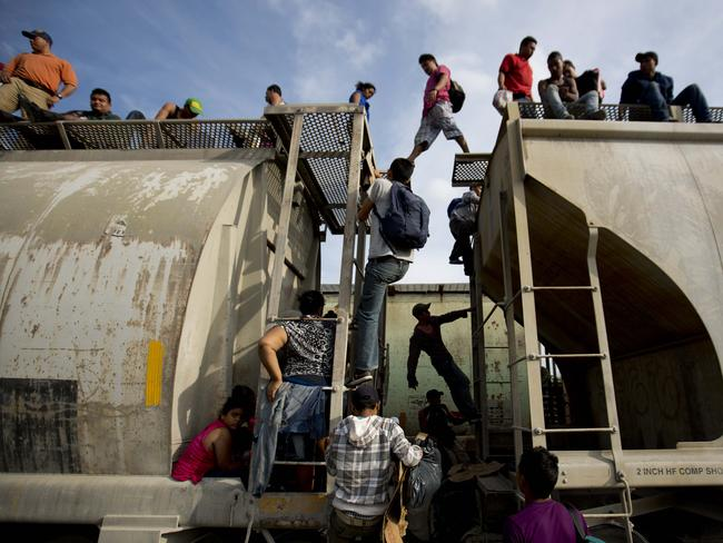 Central American migrants ... climb on a north bound train for the US border. Picture: Eduardo Verdugo