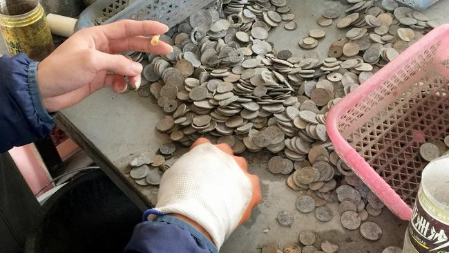 Damaged coins are pulled from piles of metal scrap. Picture: FormerFedsGroup.com