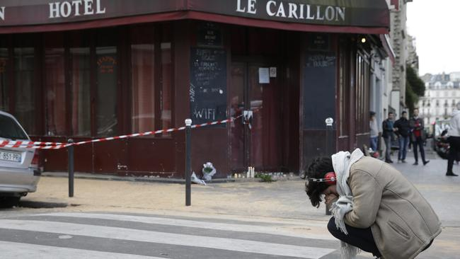 Tears for Paris ... A woman grieves outside of the Carillon bar in the 10th district of Paris. Picture: AFP