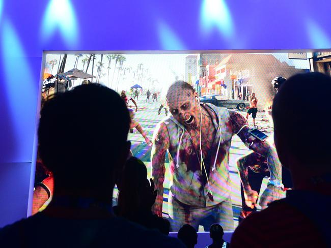 We are what we pretend to be ... gaming fans watch a preview of the game 'Sunset Drive' at the annual E3 video game extravaganza in Los Angeles, California. Picture: Frederic J Brown