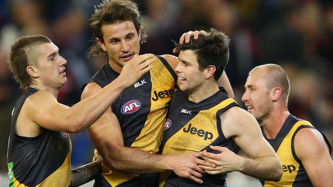 Dustin Martin, Ivan Maric and Trent Cotchin celebrate a Tiger goal.