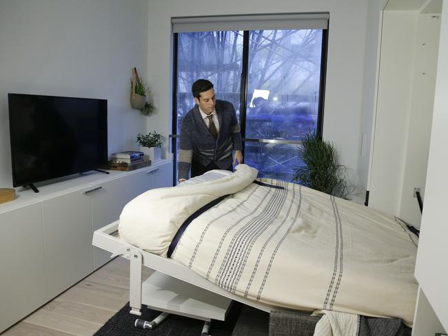 Christopher Bledsoe demonstrates a retractable bed that turns into a sofa when stored inside one of the apartment units. Picture: Julie Jacobson