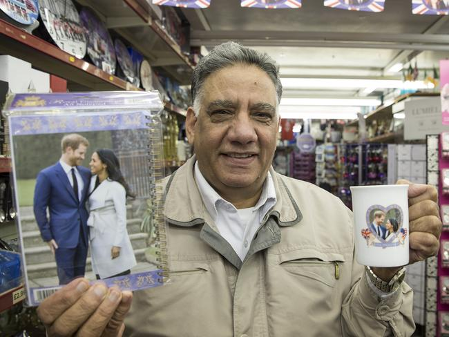Shop-keeper Malkit Aujla with souvenirs commemorating the upcoming wedding of Prince Harry and Meghan Markle. Picture: Ella Pellegrini