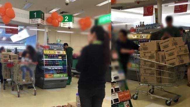A Melbourne mother snapped this picture of a group of four taking almost every tin of a rare baby formula from a Woolworths store at Epping Plaza.