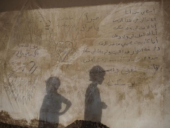 """The shadows of two boys are seen on the side of a tent inside the Khazer camp for displaced people in Northern Iraq. A poem is written in the side of the tent: """"Ask me who I am, I am talking for myself. I am the one who doesn't have a house or a home. I'm the one without relatives and a country. I used to have a house protecting me from the treason of time. In a moment this house collapsed and there's soothing left for me. I had to choose between the flames of war and the consequences of displacement. I chose displacement and the tent became my home."""""""