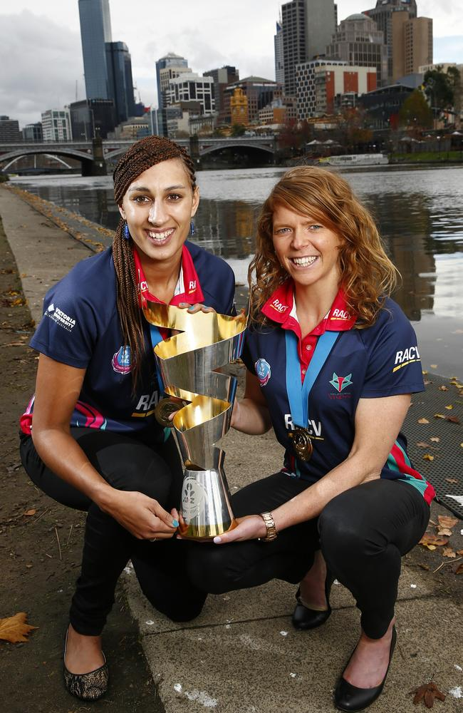 Vixens goalkeeper Geva Mentor and goal attack Tegan Caldwell with pose the trophy on the Yarra.