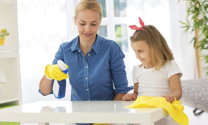 Mother and child cleaning table with mop