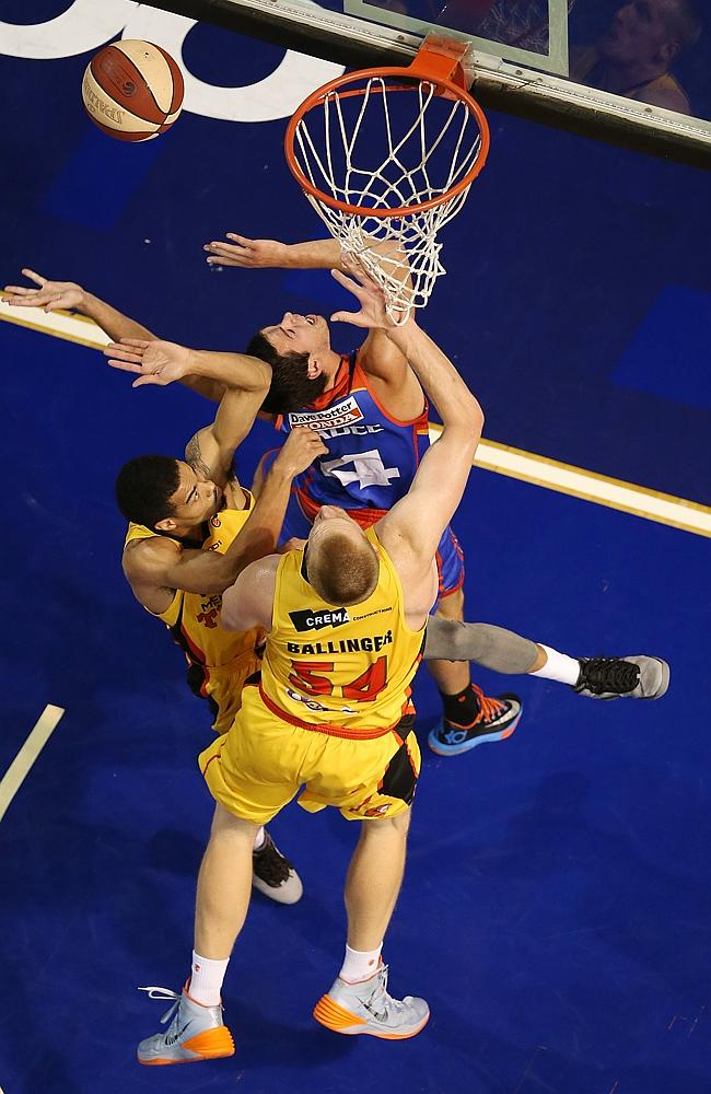 Jason Cadee of the 36ers scores despite the attention of two Tigers players under the hoop.