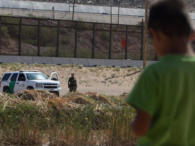 A new hope ... a Mexican boy looks at a member of the US Border Patrol standing guard on the border between El Paso in the United States and Ciudad Juarez in Mexico. Picture: Jesus Alacazar