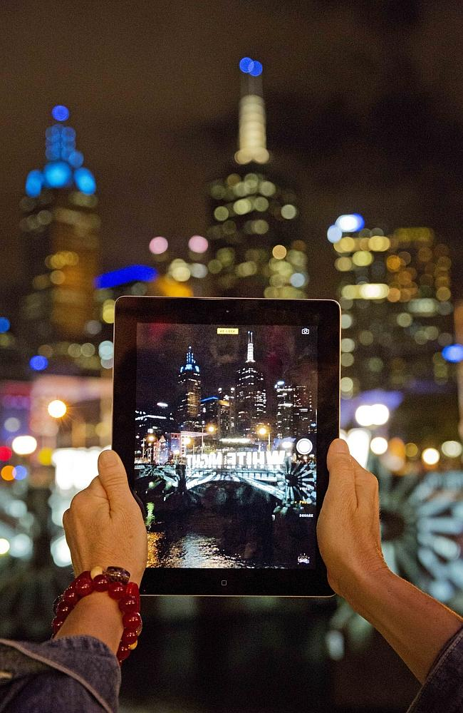 A walker tries to capture White Night on an iPad. Picture: Nathan Dyer