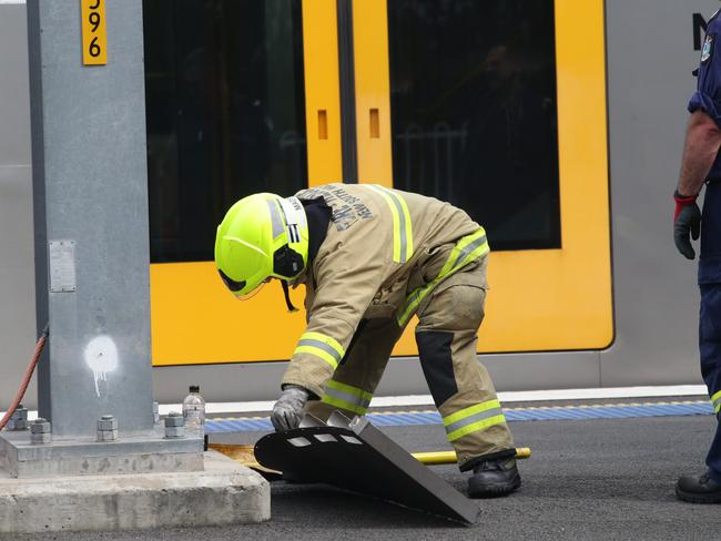 A fire and rescue crew member removes one of the train's roof hatch parts. Picture: Craig Wilson