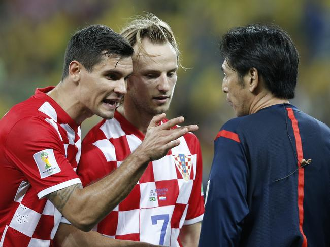 Croatia's defender Dejan Lovren (L) and Croatia's midfielder Ivan Rakitic in a heated exchange with Japanese referee Yuichi Nishimura during a Group A match between Brazil and Croatia.