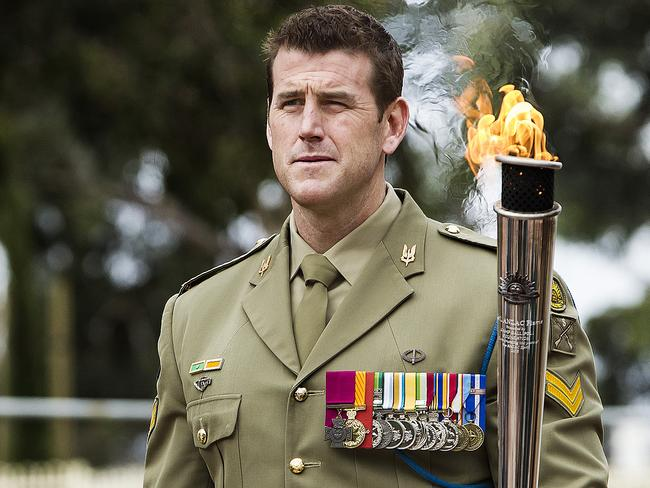VC winner Ben Roberts Smith holds the Anzac Flame.