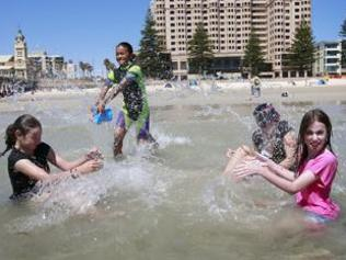 Asylum-seeker Arzoo Bahram, 13, at Gleneg beach in Adelaide with new friends Brittany Drack, 14, Rhiannon Drack, 16, and Sarah Drack, 11. Picture: Andrea Laube.