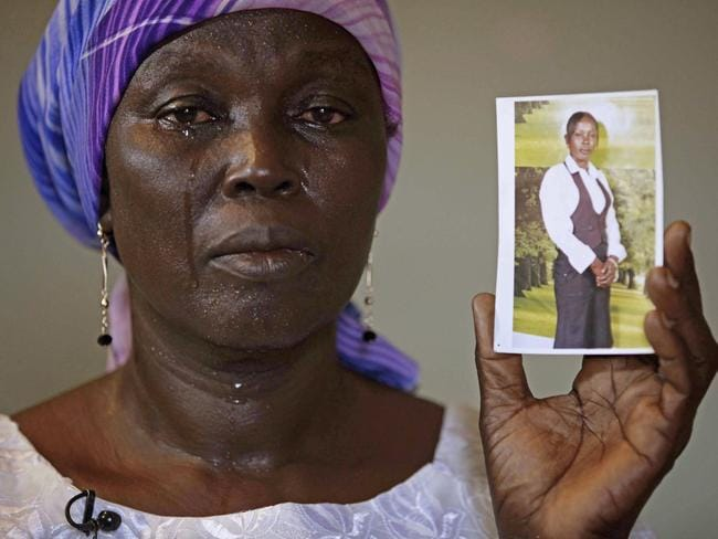 A mother's love ... Mother of kidnapped school girl Monica Mark cries as she display her photo in the family house, in Chibok, Nigeria.