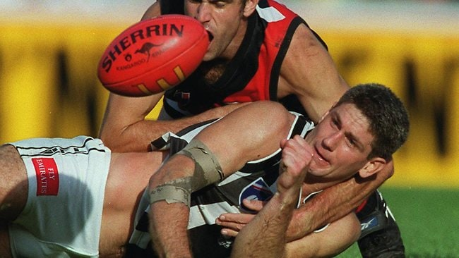 Gavin Crosisca handballs while being tackled by Essendon's Scott Lucas. Picture: George Salpigtidis