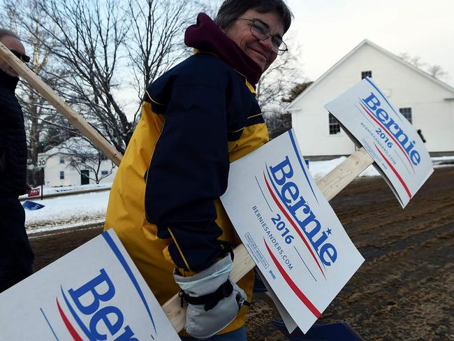 A supporter of US Democratic presidential candidate Bernie Sanders arrives with campaign posters outside the town hall of Canterbury, New Hampshire. Picture: AFP