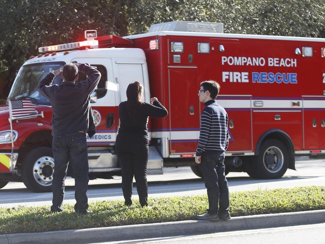 Anxious family members watch a rescue vehicle pass by after the shooting at Marjory Stoneman Douglas High School. Picture: AP Photo/Wilfredo Lee
