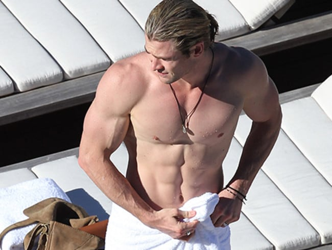 Chris shows off his muscles by a pool in Sydney. Picture: Splash