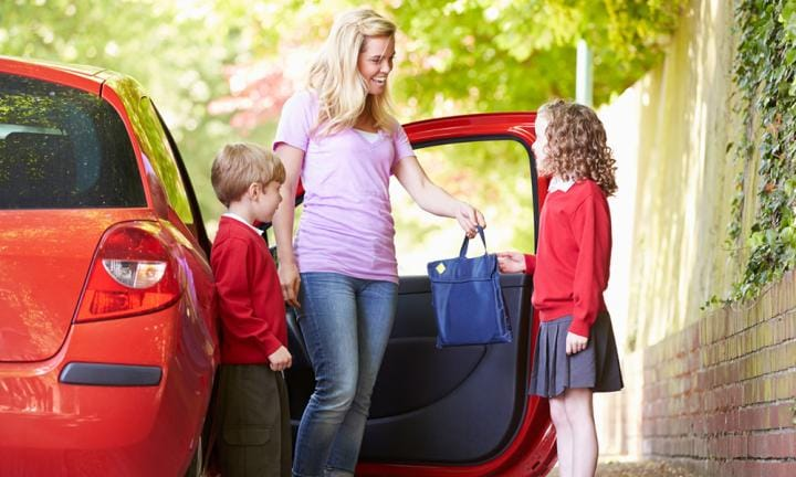 Mother and children in school uniform next to red car
