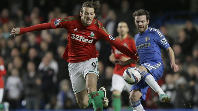 Chelsea's Juan Mata, right, gets the ball away from Swansea City's Michu during their English League Cup semi-final first leg at Stamford Bridge. Swansea won 2-0. Picture: Alastair Grant