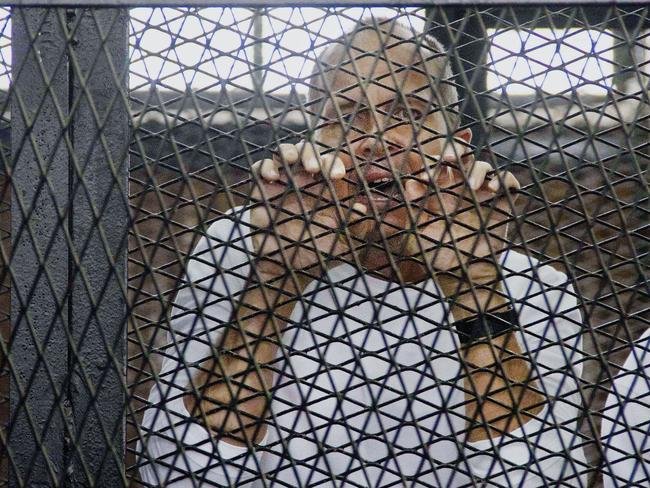 Desperate ... the award-winning Peter Greste in a defendants' cage before his sentencing.