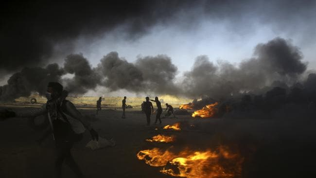 Palestinian protesters burn tires during a protest at the Gaza Strip's border with Israel, east of Khan Younis, Picture: AP