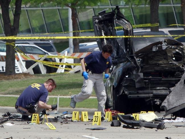 Wreckage ... FBI investigators beside the wreckage of parked car in front of the Curtis Culwell Center on Monday. Picture: Ben Torres/Getty Images