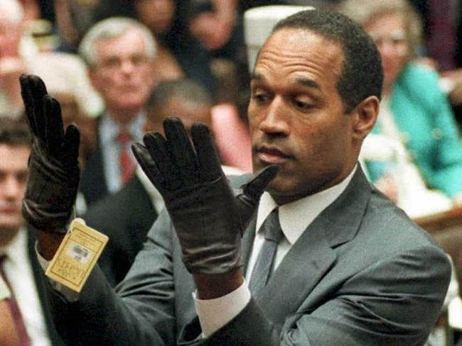 OJ Simpson looking at a new pair of gloves that prosecutors had him put on during his double-murder trial in Los Angeles: AFP PicVince/Bucci