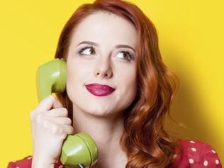 Smiling redhead girl in red polka dot dress with green dial phone on yellow background.