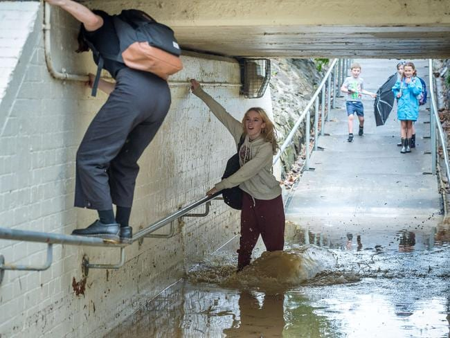 Commuters navigate a flooded underpass at Northcote train station. Picture: Jake Nowakowski