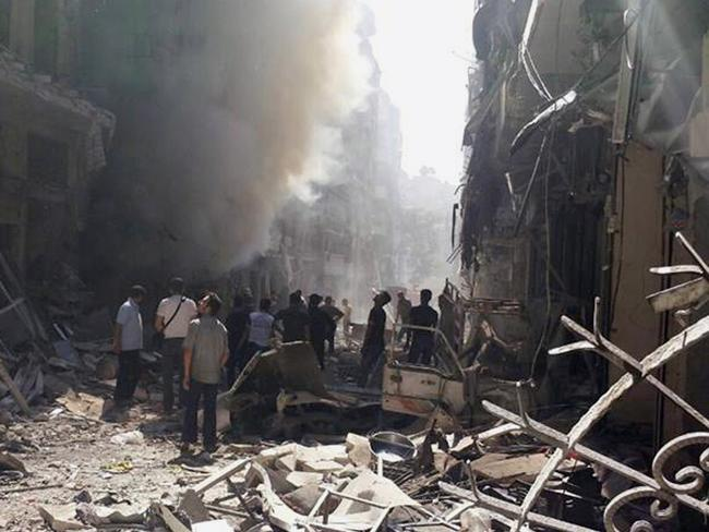 Neighbourhood battles ... Syrians walk amid the rubble of destroyed buildings following a Syrian government airstrike at Karm al-Jabal area in Aleppo. Picture: Syrian Observatory for Human Rights