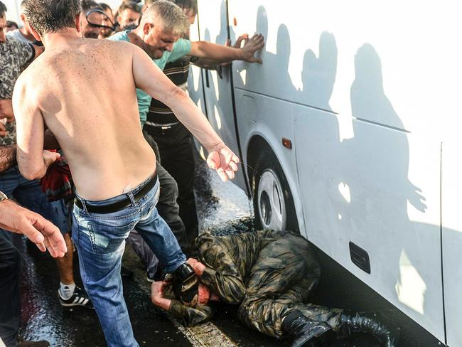 People beat a soldier up on the ground after taking over a military position on the Bosphorus bridge in Istanbul on July 16. Picture: Selcuk Samiloglu